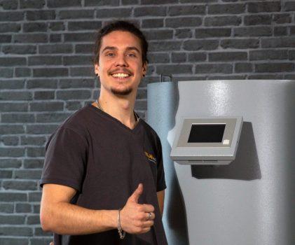 Kundendiensttechniker Phillip vor der SOLARvent Pelletheizung iQ 3.0